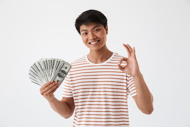 Портрет возбужденного молодого азиатского мужчины, держащего деньги