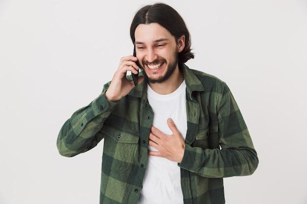 Портрет возбужденного молодого бородатого мужчины в повседневной одежде, стоящего изолированно над стеной и разговаривающего по мобильному телефону