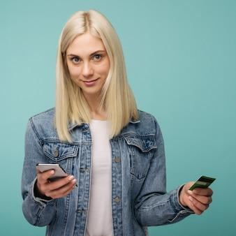 Портрет возбужденной молодой блондинки показывает пластиковую кредитную карту, держа мобильный телефон над синим