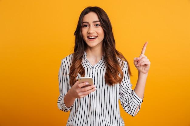 Портрет взволнованной молодой девушки, держащей мобильный телефон