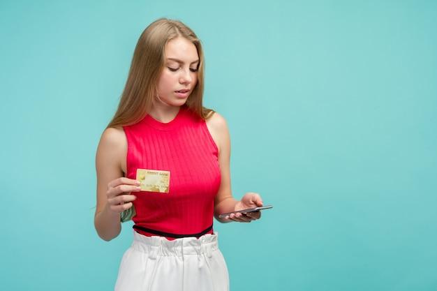 プラスチックのクレジットカードを示す興奮した少女の肖像画