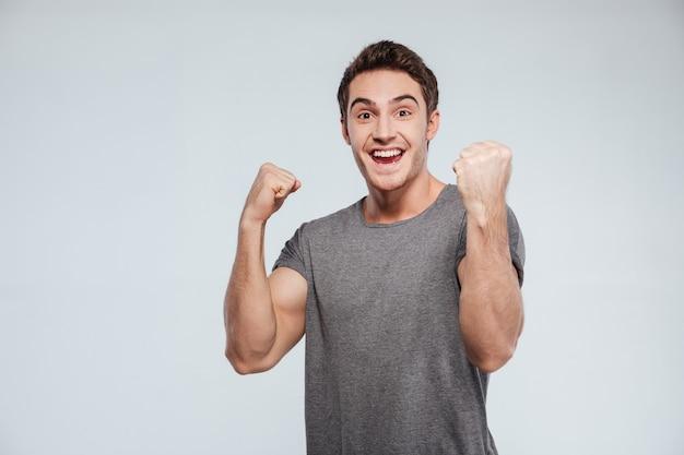灰色の空中で2つの拳で成功を祝う興奮した若い男の肖像画