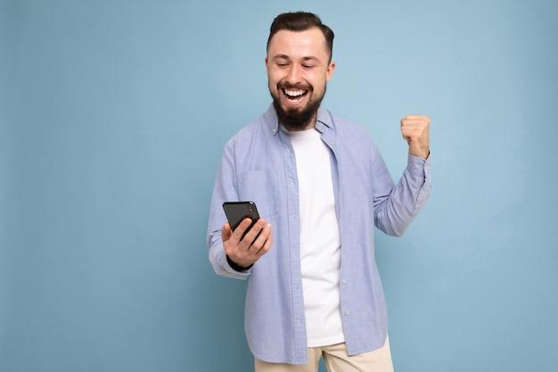 Портрет возбужденного молодого человека, смотрящего на мобильный
