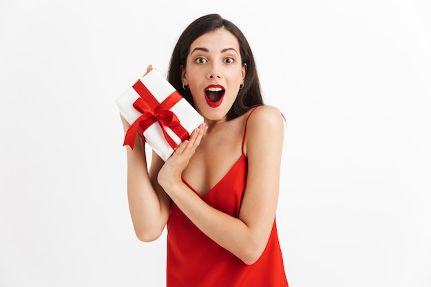 고립 된 선물 상자를 들고 빨간 드레스에 흥분된 젊은 여자의 초상화