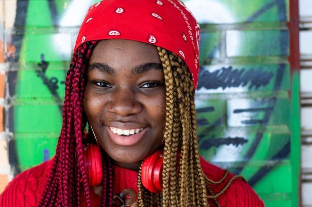 색된 머리 띠와 이국적인 흑인 여자의 초상화. 목에 매달려있는 빨간 헤드폰. 빨간 스웨터와 빨간 머리 스카프를 입고. 낙서 벽