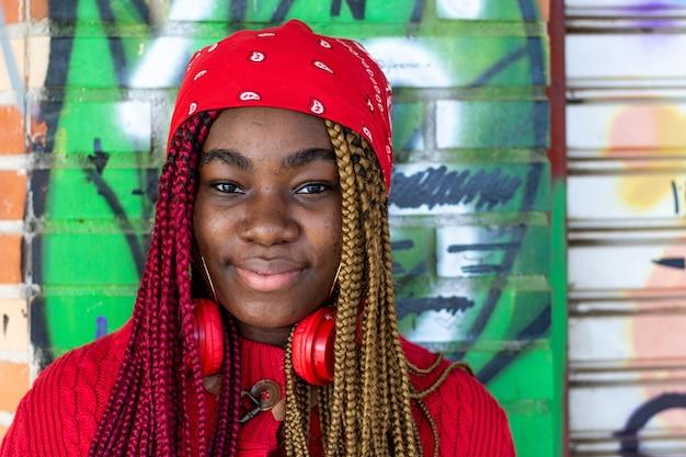 색된 머리 띠와 이국적인 흑인 여자의 초상화. 목에 매달려있는 빨간 헤드폰. 빨간 스웨터와 빨간 머리 스카프를 입고. 낙서 벽에 기대어.