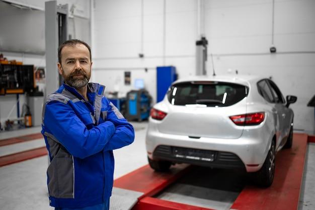 サービスとメンテナンスのために車両ワークショップに立っている経験豊富な中年のひげを生やした自動車整備士の肖像画。