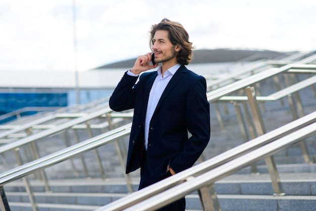 Портрет красивого бизнесмена с телефоном, чашкой кофе на улицах города