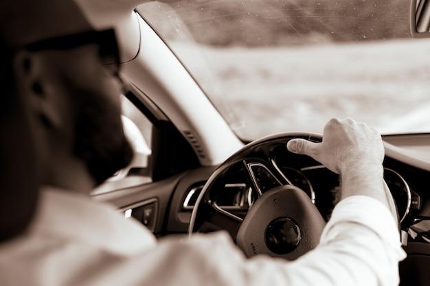 그의 차를 운전하는 잘 생긴 남자의 초상화 스타일과 지위의 수염 난 남자 잘 생긴 젊은 남자