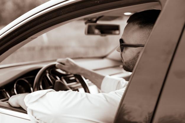 그의 차를 운전하는 잘 생긴 남자의 초상화 스타일과 지위의 수염 난 남자 잘 생긴 젊은