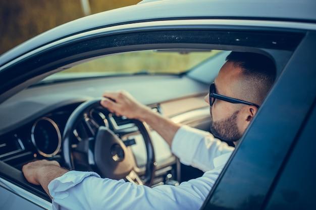 그의 차를 운전하는 잘 생긴 남자의 초상화 스타일과 지위의 수염 난 남자