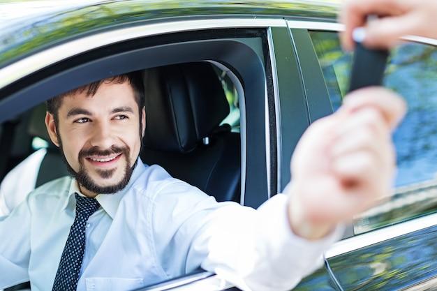 그의 차를 운전하는 잘 생긴 행복한 사업가의 초상화