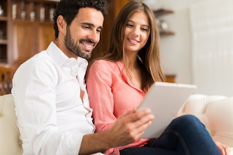 Portrait of an happy couple using a tablet.