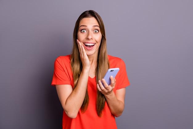Портрет впечатленной сумасшедшей девушки, использующей свой смартфон в красивом наряде, изолировал стену серого цвета