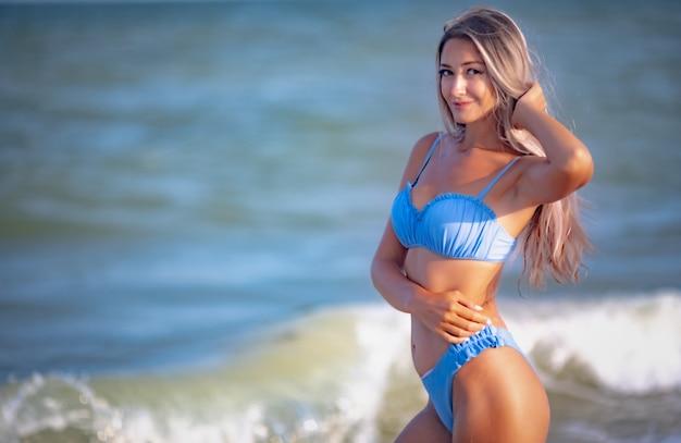 Портрет неописуемой красавицы со стройным телом и роскошными светлыми волосами в нежно-голубом купальнике.