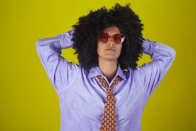 メガネとメンズシャツと黄色の壁にアフロの巻き毛のヘアスタイルとネクタイでインドの少女の肖像画