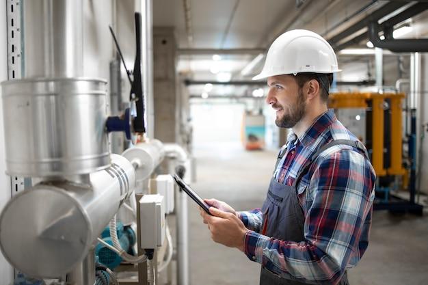 工場のボイラー室の保護ユニフォームとヘルメットチェックバルブとガス設備の産業エンジニア労働者の肖像画。