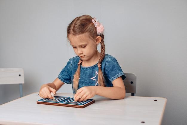白いテーブルに座ってパズルを解く、知的な、機知に富んだ、焦点を絞った小さな子供の肖像画。濃度の概念。ノイズのある写真