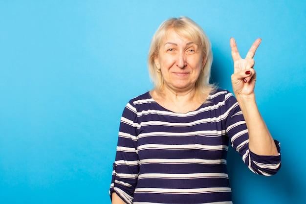 Портрет старой дружелюбной женщины в вскользь футболке делает дружелюбный жест двумя пальцами вверх на изолированной голубой стене. эмоциональное лицо. концепция партии
