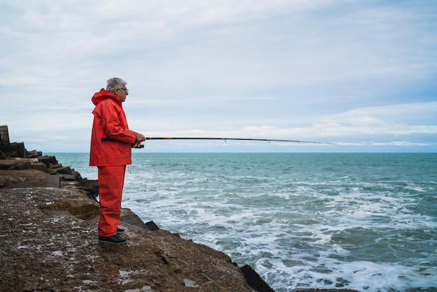 Портрет старика, ловящего рыбу в море. концепция рыбалки.