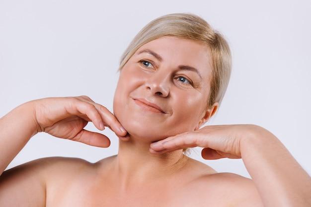 繊細で清潔な顔の肌に手を当てて触る老婆のポートレート