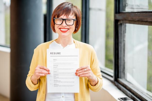 창 근처에 실내에 서 있는 보험 문서를 들고 있는 행복한 나이든 여성의 초상화