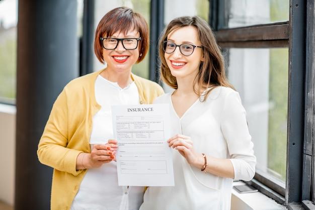 창가 근처에서 실내에서 보험 문서를 들고 있는 딸과 함께 행복한 나이든 여성의 초상화