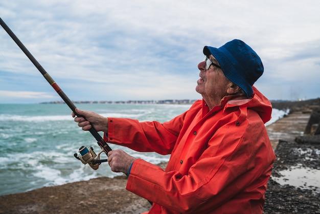 人生を楽しんで、海で釣りをしている年配の男性の肖像画。釣りとスポーツのコンセプト。