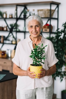 Portrait of an smiling woman holding yellow pot plant in hands