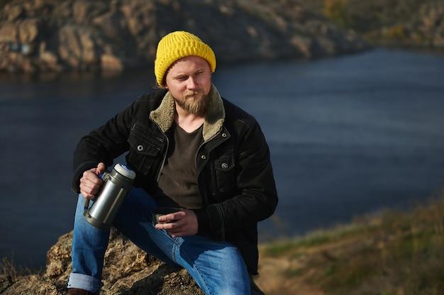 Портрет путешественника, сидящего на скалах с термосом, наливающего в чашку теплого напитка и отдыхающего во время прогулки на природе. скалы и озеро