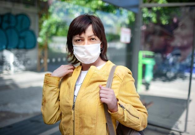 Портрет неизвестной молодой женщины в маске, позирующей на открытом воздухе во время пандемии коронавируса в солнечный теплый летний день