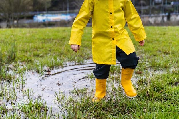 Портрет до неузнаваемости малыша в луже дождевой воды на лужайке на лугу в желтом плаще и желтых резиновых сапогах