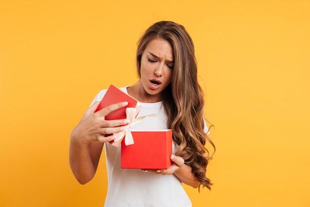 Портрет расстроенной разочарованной девушки, открывающей подарочную коробку
