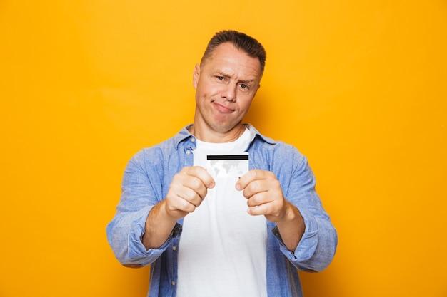 クレジットカードを示す動揺した中年男性の肖像画