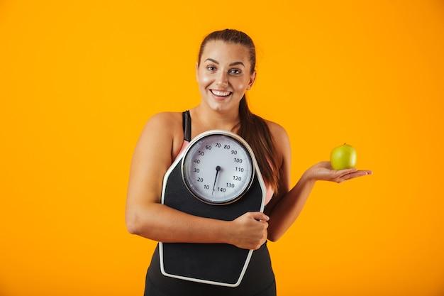 Портрет расстроенной полной молодой женщины в спортивной одежде, стоящей изолированно над желтой стеной, держащей зеленое яблоко и весы