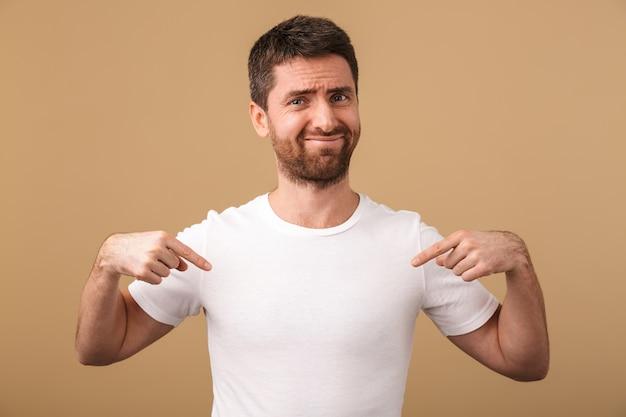 화가 젊은 남자의 초상화는 그의 공백 t- 셔츠에 손가락을 가리키는 베이지 색 위에 고립 된 서 부담없이 옷을 입고