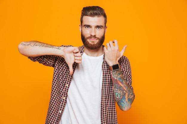 아래로 스마트 시계 엄지 손가락을 보여주는 캐주얼 옷을 입고 화가 젊은 남자의 초상화