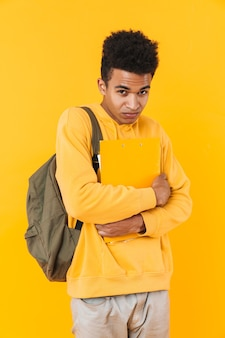노란 벽에 고립되어 배낭과 교과서를 들고 서 있는 화가 난 십대 소년의 초상화