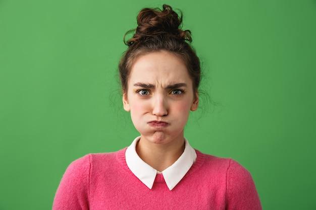 Портрет расстроенной молодой женщины, стоящей изолированной над зеленым
