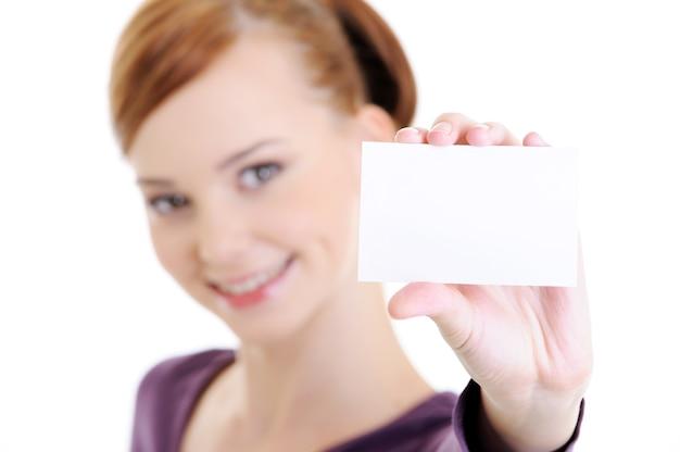 空白の白いカードを持つ若い美しい幸せな女性の肖像画