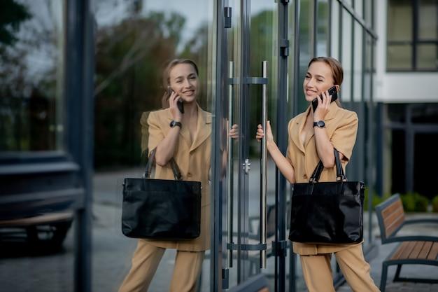 若い成功した実業家の肖像画は、オフィスの近くのカメラでの彼女の仕事に満足して笑っています。