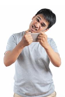 회색 티셔츠를 입은 화난 아시아 남자의 초상화는 흰색 배경에 격리된 스마트폰에 화를 낸다