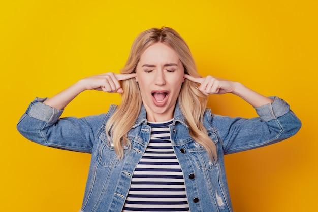 Портрет сердитой избегающей девушки кричать с открытым ртом и закрывать уши на желтом фоне