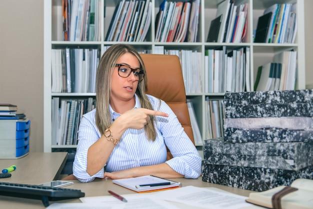 Портрет разъяренной блондинки-секретарши, указывающей на стопку папок, ожидающих архивации на своем рабочем столе