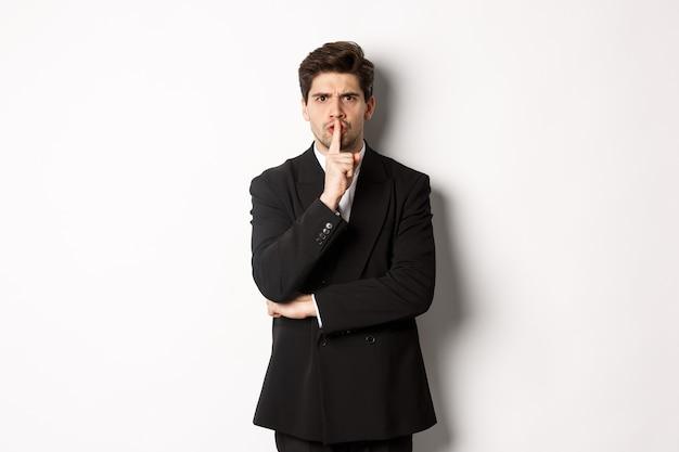 白い背景の上に立って、あなたに向かって身をかがめ、静かに言って、タブーの静けさのサインと眉をひそめているスーツを着た怒っている上司の肖像画。