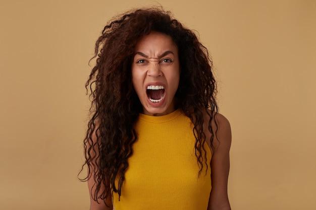カメラを見ながら狂ったように叫び、ベージュの背景の上にポーズをとっている間彼女の手を下に保つ怒っている茶色の髪の巻き毛のブルネットの女性の肖像画