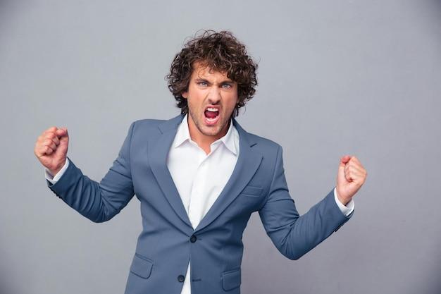 Портрет разгневанного бизнесмена, кричащего над серой стеной
