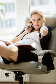 Портрет сердитой деловой женщины, сидящей на стуле и указывающей пальцем