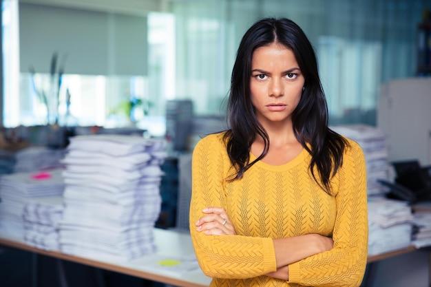 Портрет сердитой бизнес-леди, стоящей со сложенными руками в офисе