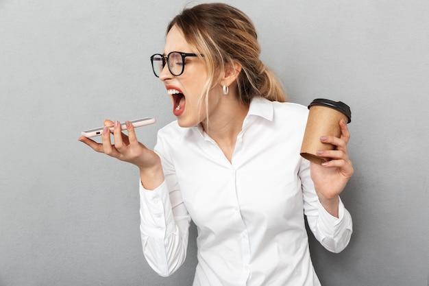 携帯電話で叫んで、オフィスでコーヒーを保持し、孤立した眼鏡をかけている怒っている実業家の肖像画